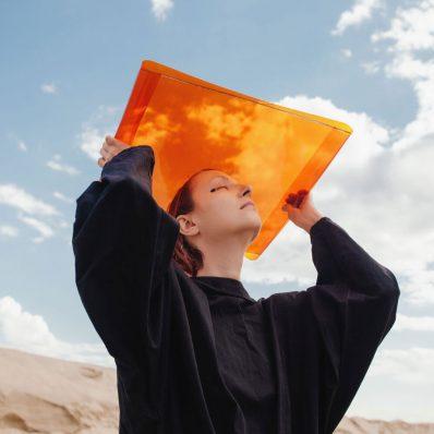 Girl holds up orange sheet against a blue sky