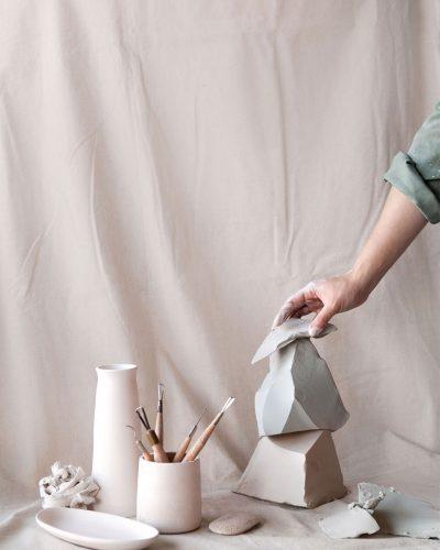 A hand arranges ceramic sculptures alongside artist tools against a pastel pink studio backdrop