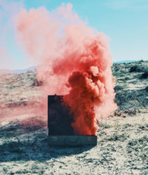 A cloud of pink smoke billows out of a suitcase