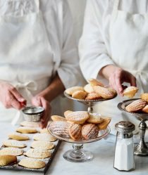 Two chefs prepare and dust dishes of madeleines with sugar